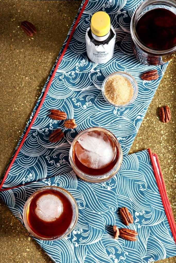Overhead image of two Toasted Pecan Old Fashioneds, sitting on a blue-and-white dishtowel on a gold glittery tray with the ingredients.