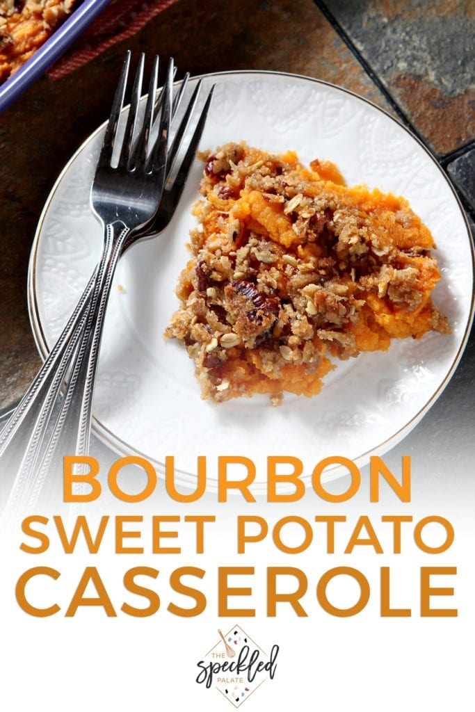 Close up of a white plate holding a serving of Bourbon Sweet Potato Casserole next to two silver forks with the text 'bourbon sweet potato casserole'