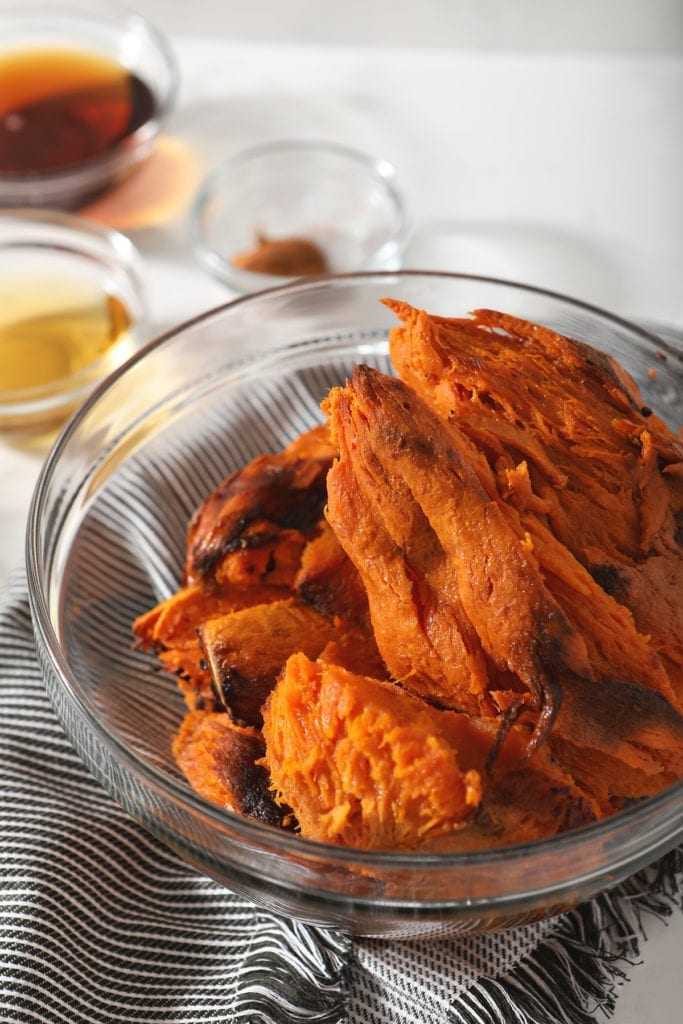 Baked sweet potatoes in a glass bowl on marble