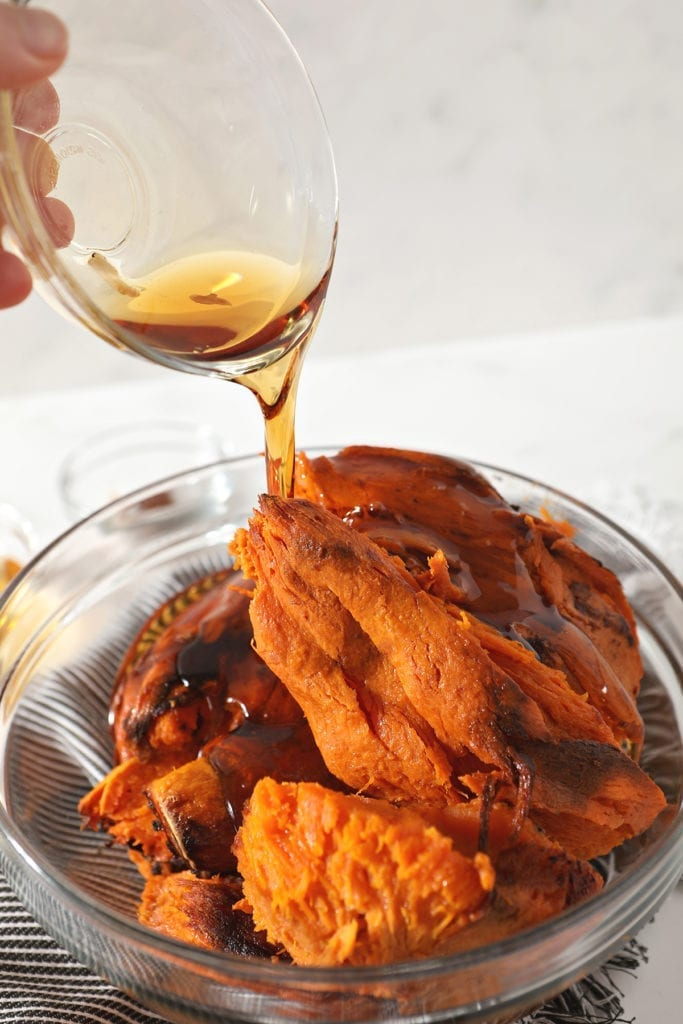 Maple syrup is poured on top of baked sweet potatoes in a bowl