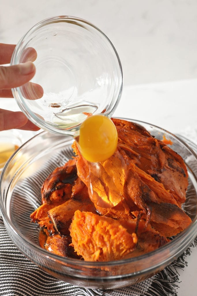 A whole egg is poured on top of baked sweet potatoes in a bowl