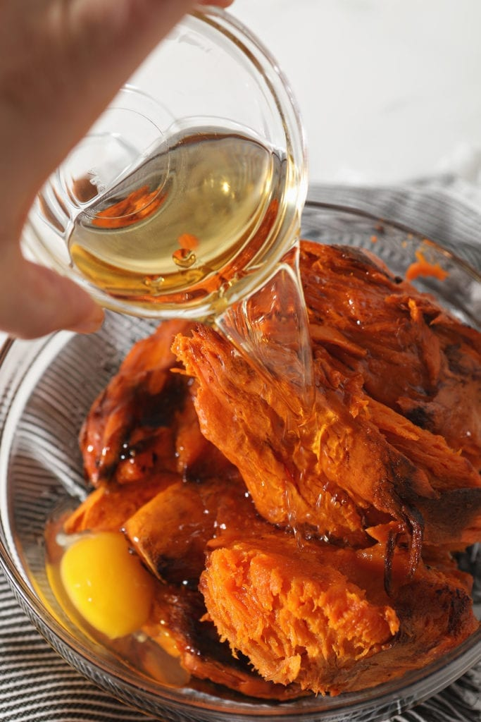 Bourbon is poured on top of sweet potatoes and other ingredients in a bowl