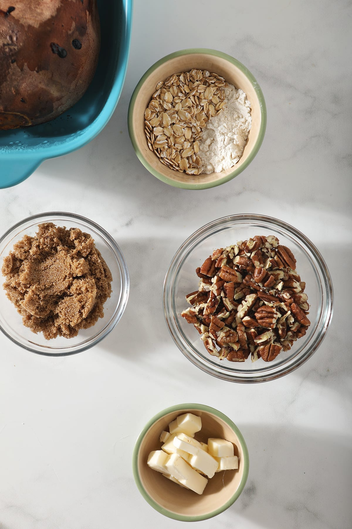 Nuts, butter, sugar and oats in bowls before making a streusel topping