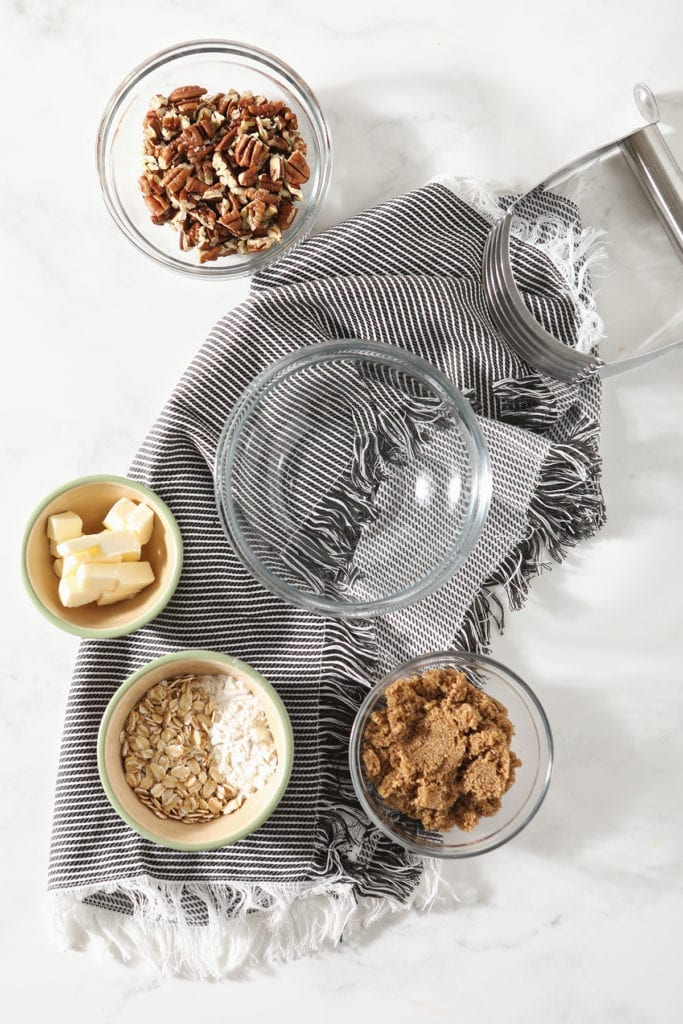 Streusel ingredients in bowls before mixing on a grey striped towel