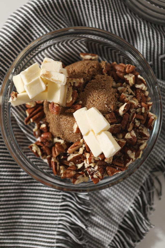 Sugar, butter, flour and pecans in a bowl before blending on a grey towel