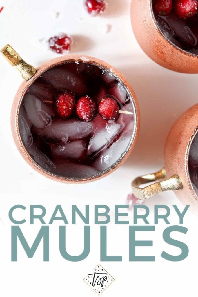 Pinterest image for Cranberry Mules, featuring a close-up overhead shot of the drink in copper mugs, garnished with sugared cranberries