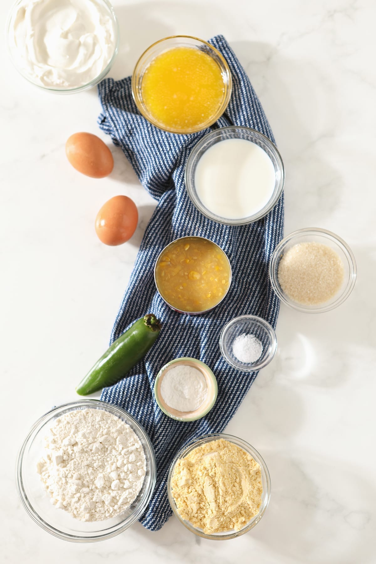 Cornmeal, flour, sour cream, butter, eggs, jalapeno and more in bowls on top of marble before the casserole is mixed