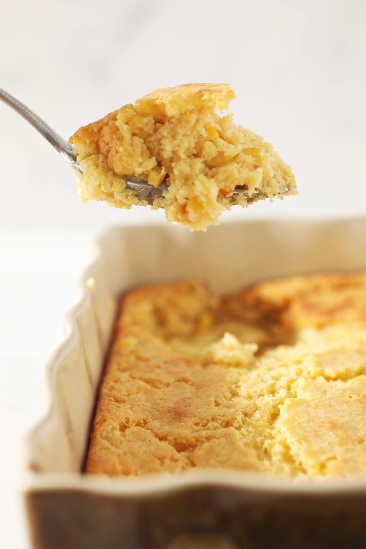 Creamed Cornbread Casserole lifted out of the dish with a silver spoon
