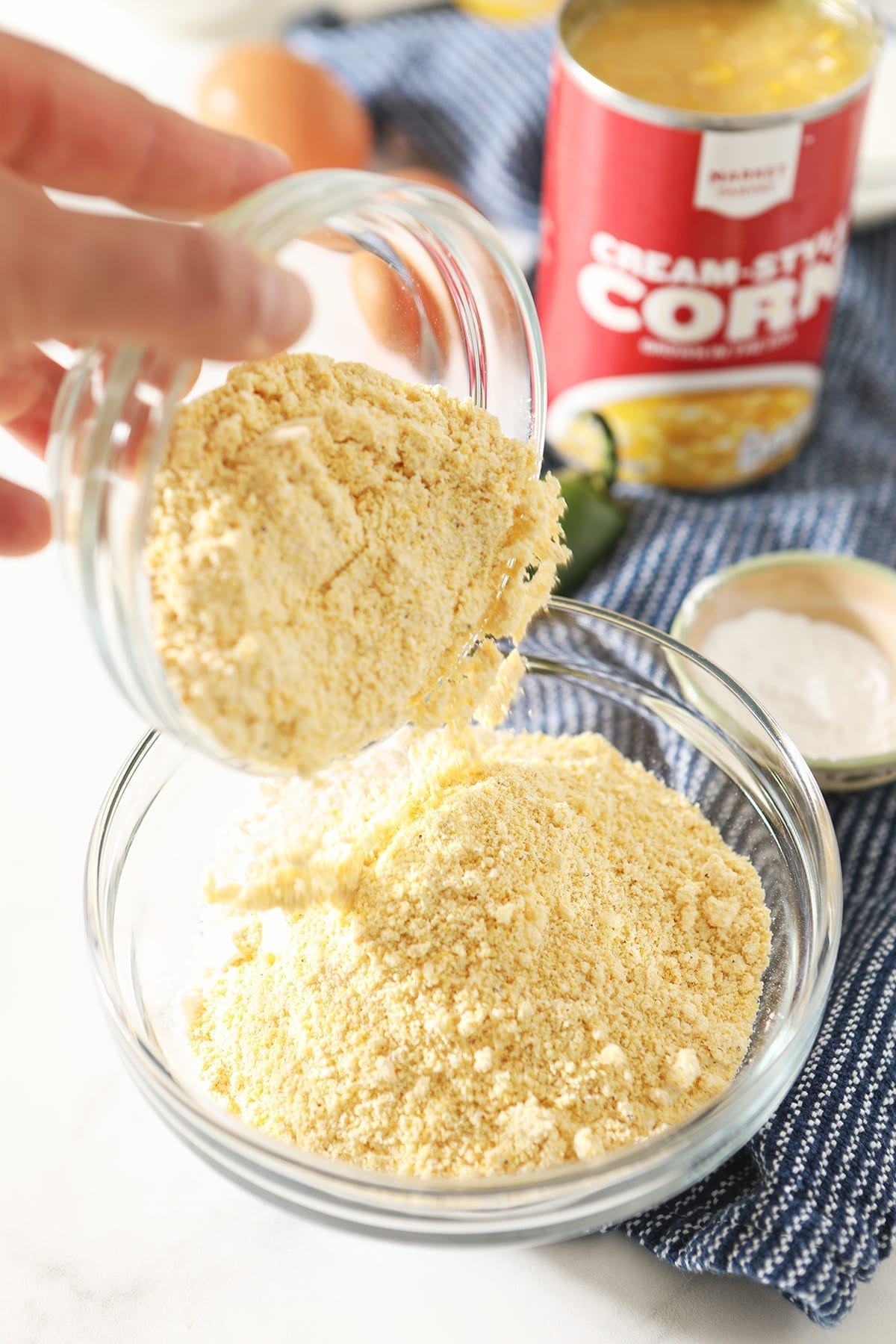 Cornmeal is poured on top of flour in a bowl