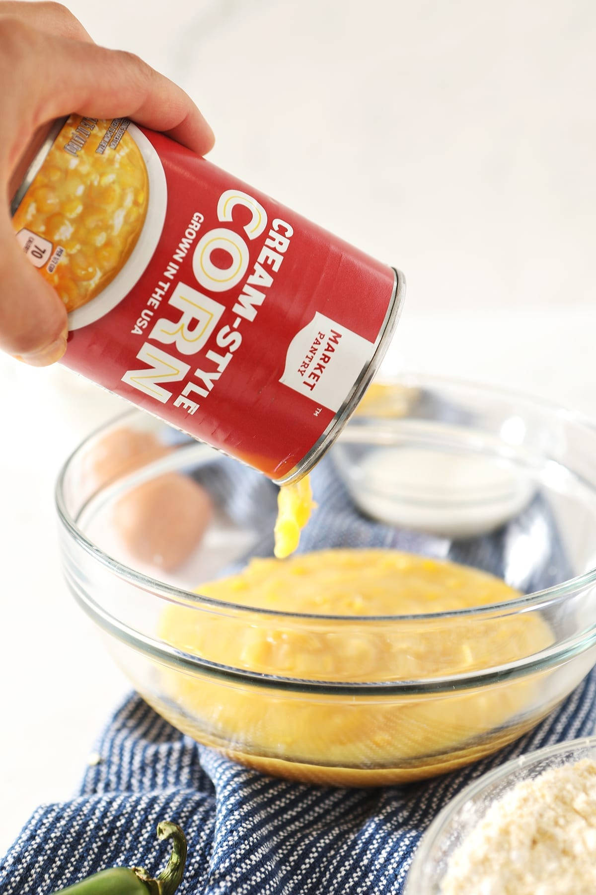 A can of creamed corn pours into a glass bowl