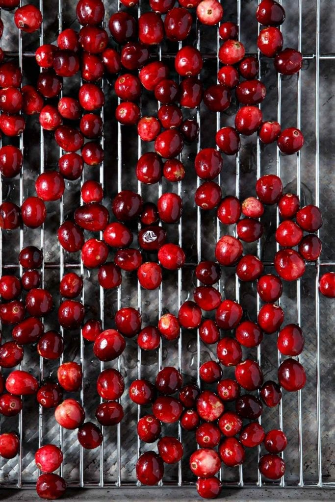 Sugar-glazed cranberries sit on a cooling rack before being tossed in sugar to make sugared cranberries