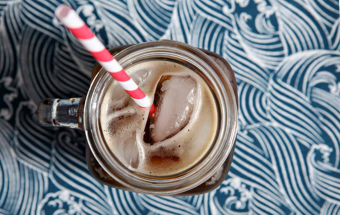 An overhead of the Boyfriend Irish Coffee in a mason jar glass, shown on a patterned blue napkin