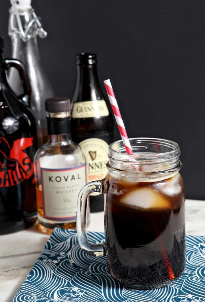 The Boyfriend Irish Coffee photographed on a light marble surface with a black background, surrounded by its ingredients