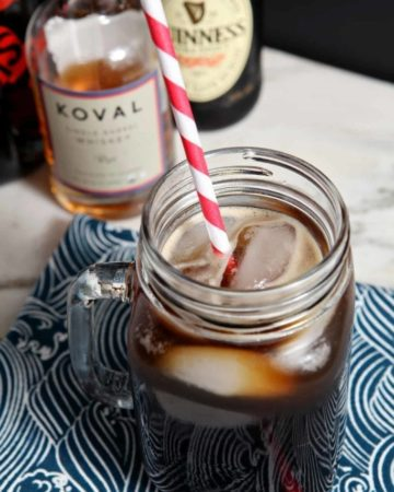 The Boyfriend Irish Coffee shown on a light marble surface with a black background, surrounded by its ingredients