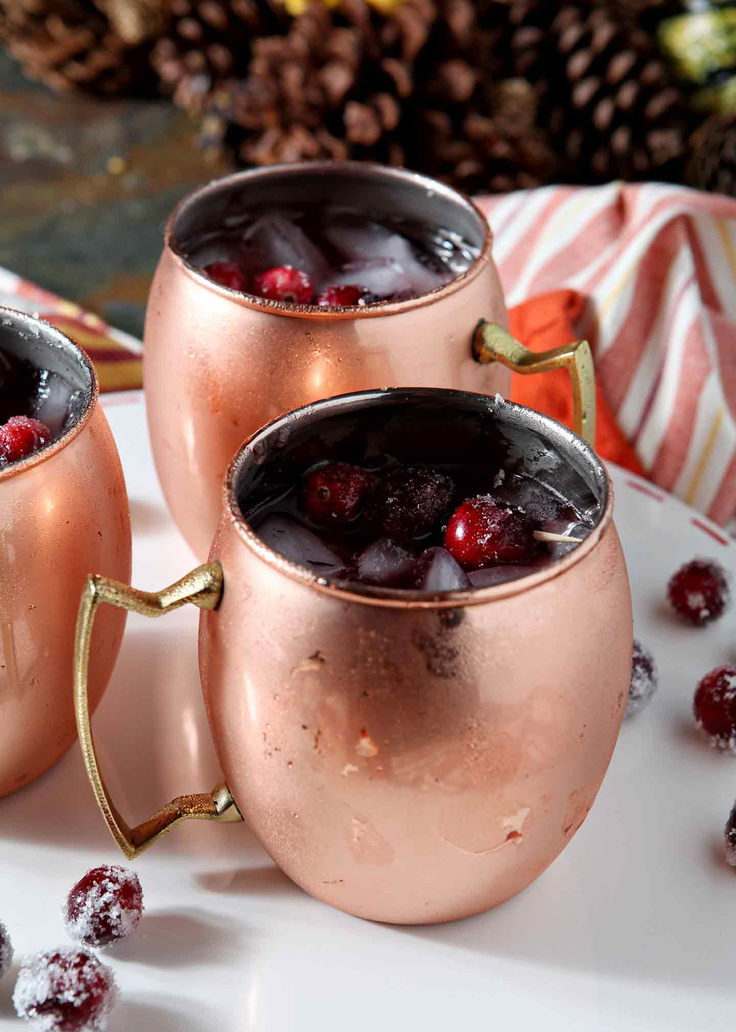 Close up of three Cranberry Mules, shown on a white serving platter