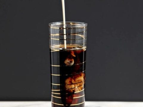 Cream pours into a coffee drink in a gold striped champagne flute