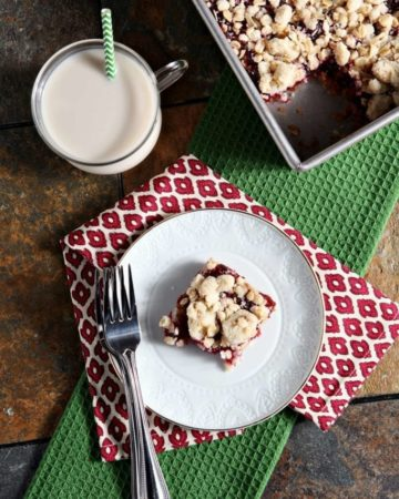 Cranberry Crumb Bar on white plate with fork and glass of milk