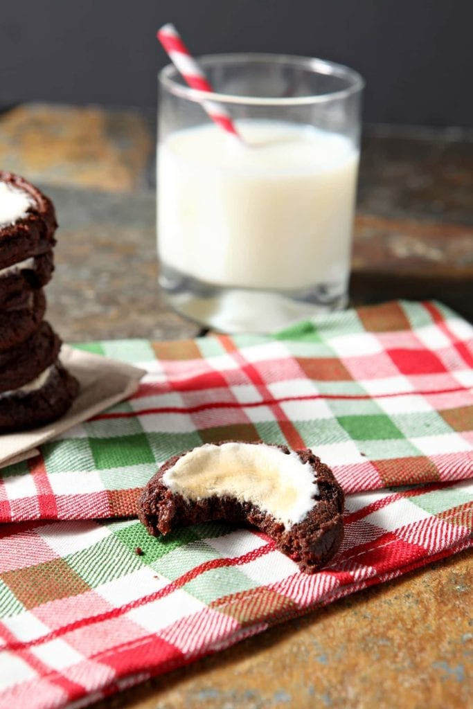 A bite out of cookie sitting on holiday linens with glass of milk