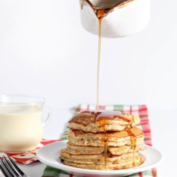 Cinnamon syrup is poured on top of Eggnog Pancakes