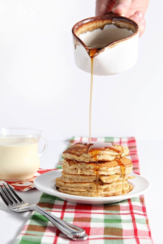 Cinnamon syrup is poured on top of a stack of Eggnog Pancakes