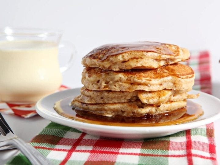 Cinnamon Syrup runs down the sides of a stack of pancakes sitting on a red and green plaid towel