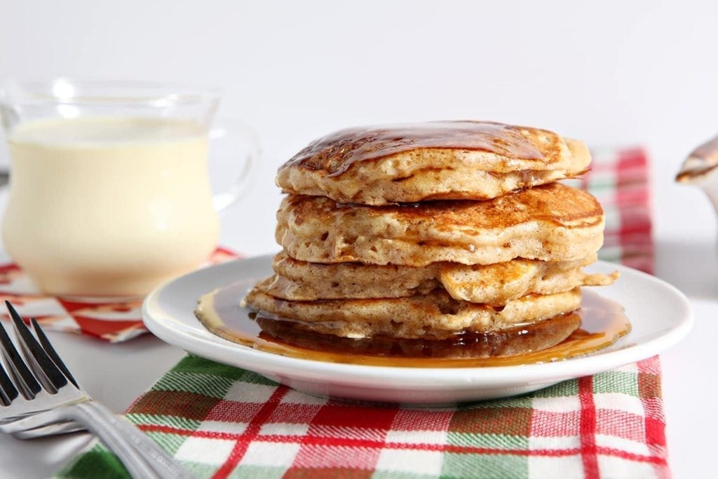 Horizontal image of Cinnamon Syrup running down the sides of a stack of Eggnog Pancakes