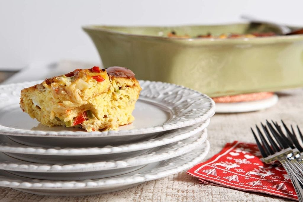 A serving of Christmas Breakfast Casserole sits on a white plate with the baking dish in the background