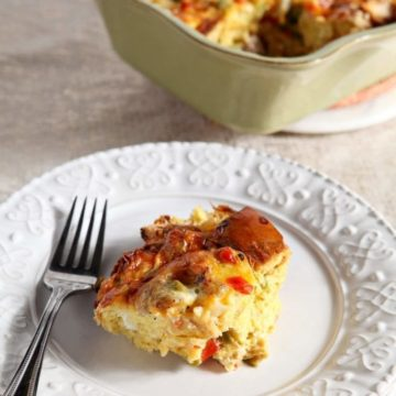 A serving of Christmas Breakfast Casserole sits on a white plate with a fork.