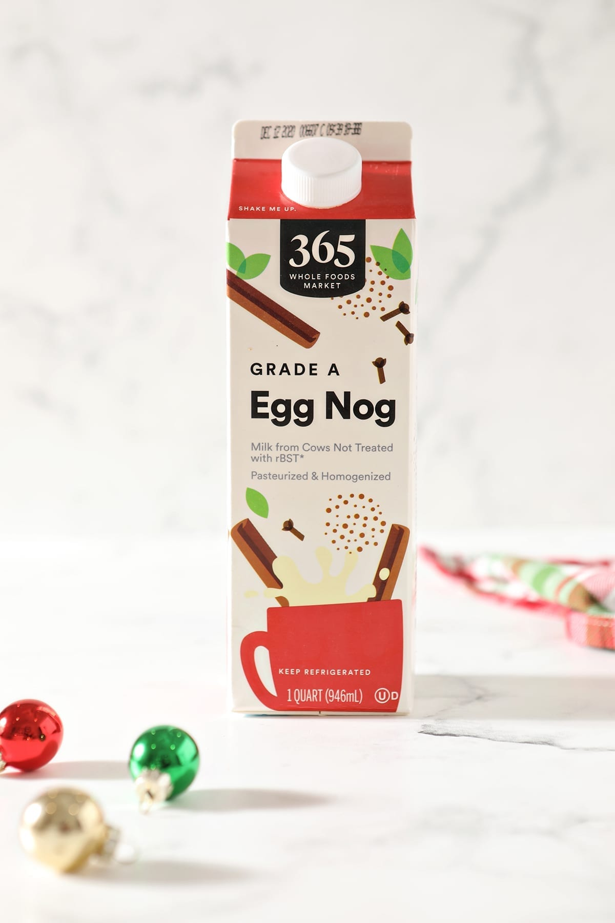 A box of 365 eggnog sits on a marble surface next to red, green and gold ornaments