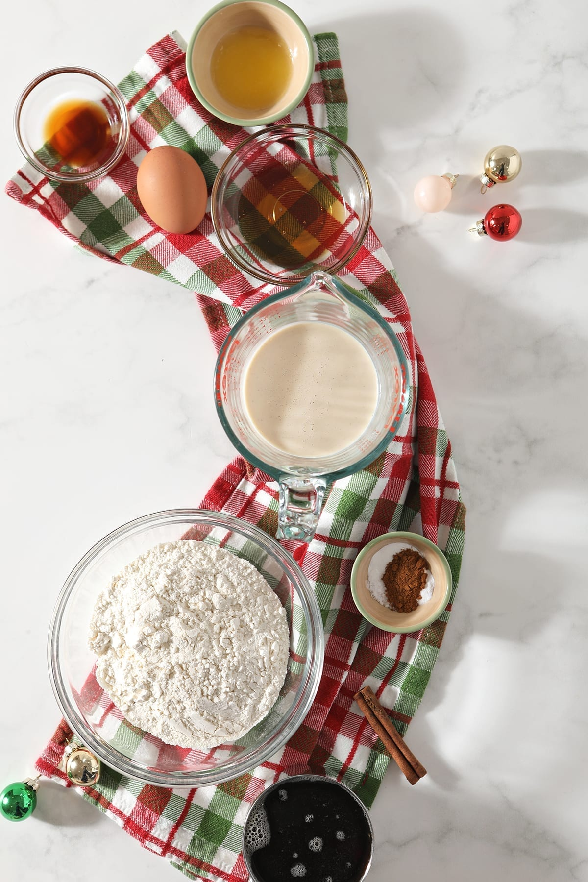 Ingredients for eggnog pancakes and the cinnamon syrup sit on top of a green and red plaid towel on marble next to small shiny ornaments