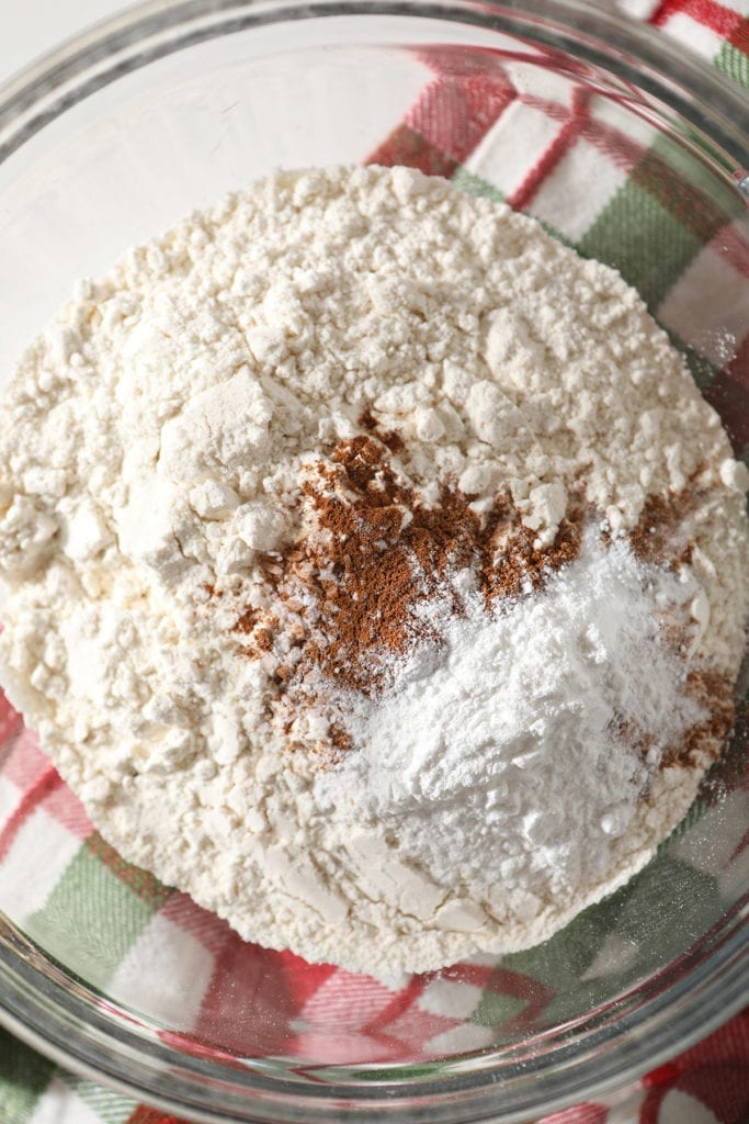 Flour, cinnamon and other dry ingredients in a clear glass bowl on top of a green and red plaid kitchen towel