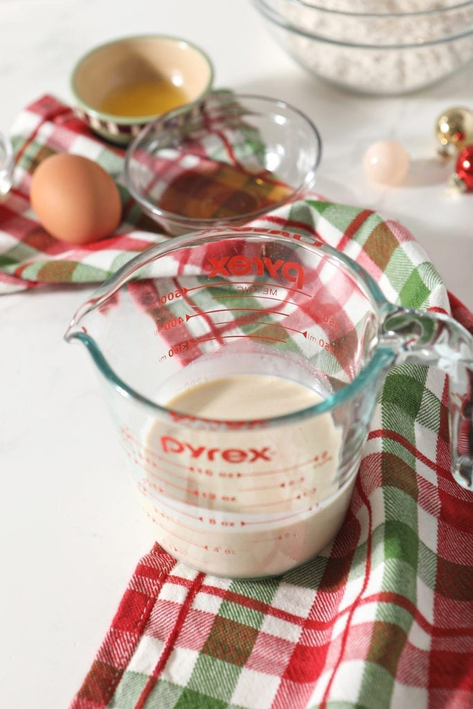 A measuring cup full of eggnog sits on top of a green and red plaid kitchen towel next to other wet ingredients