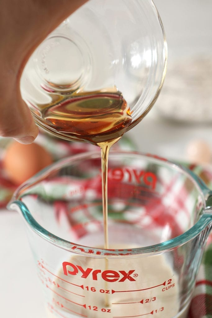 Maple syrup pours into a glass measuring cup of eggnog
