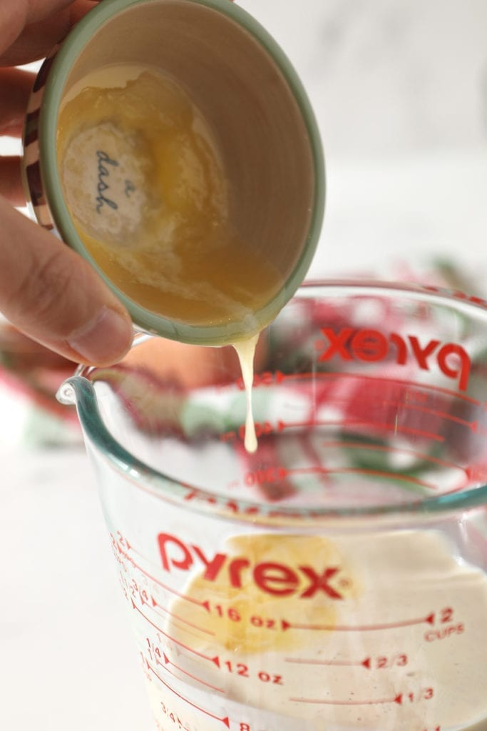 Melted butter pours into a pyrex holding other wet ingredients