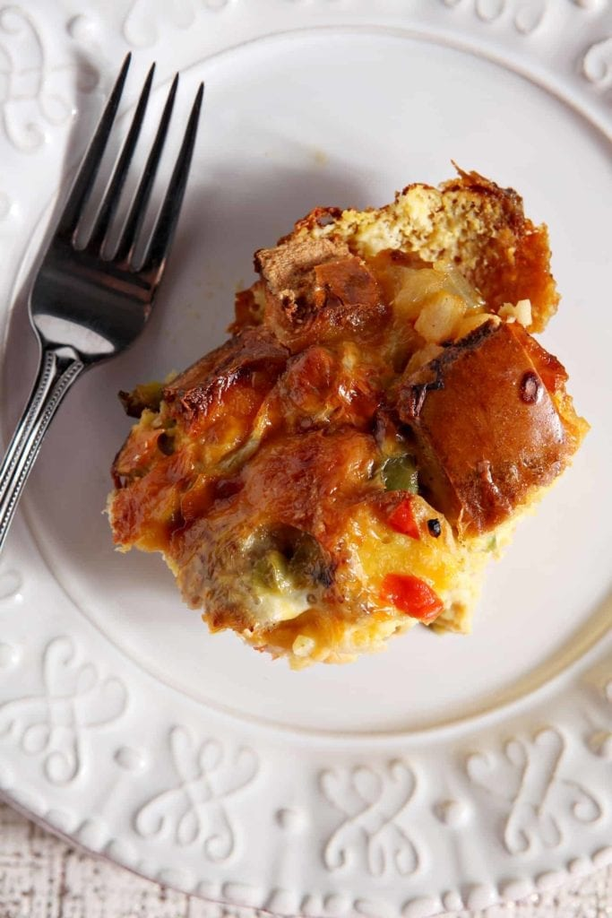 Close up of a serving of Christmas Breakfast Casserole on a white plate with a fork, shown from above
