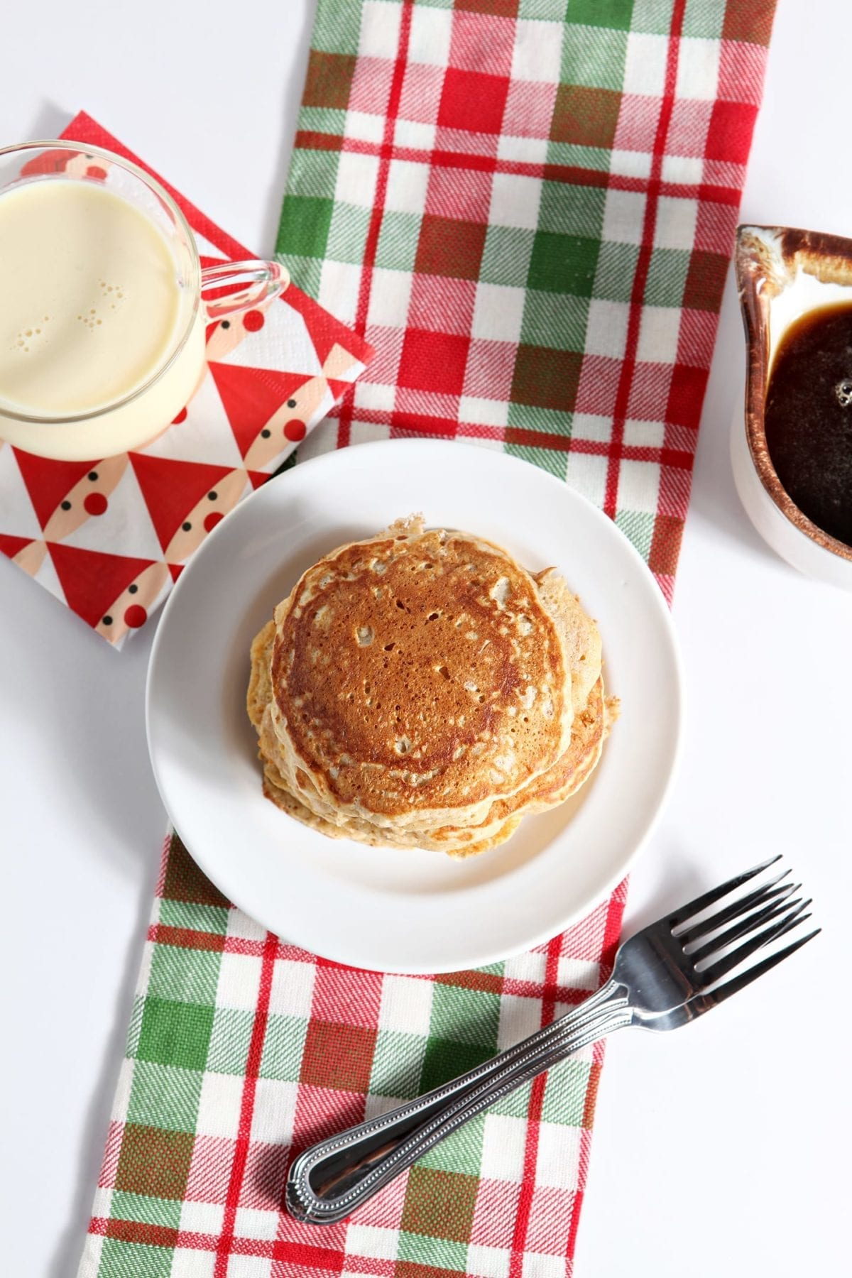 A stack of pancakes sits on a white plate sitting on a red and green plaid towel next to a cup of eggnog and syrup