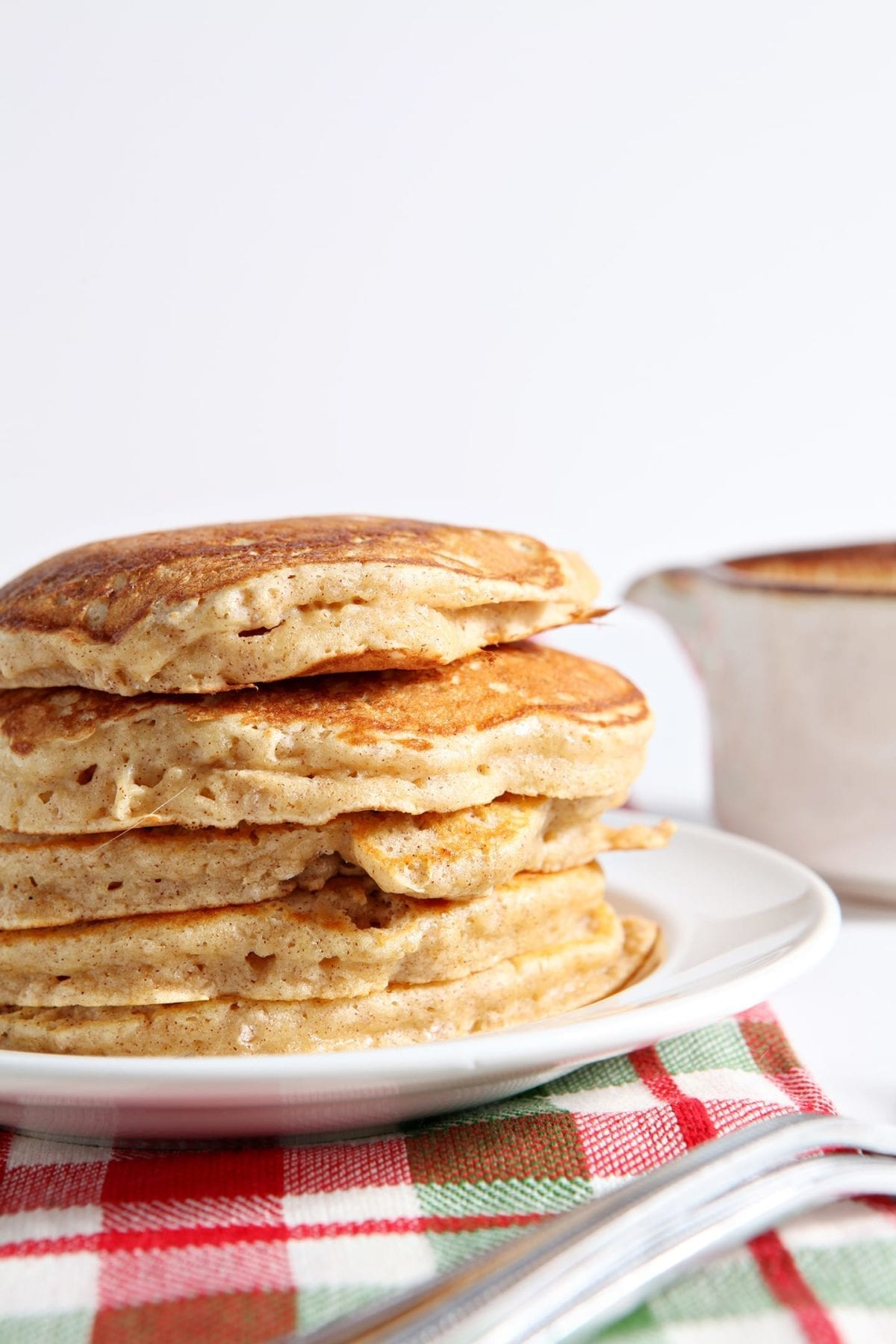 Close up of a stack of eggnog pancakes sitting on a white plate on top of a red and green plaid towel