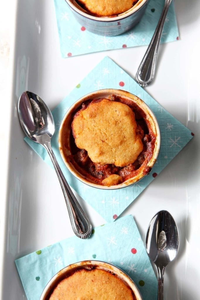 Hearty beef chili is topped with a slightly sweet homemade cornbread mix, then baked to perfection to make individual Chili Cornbread Pot Pies. Perfect for a cold winter evening, this recipe combines two well-loved chilly weather favorites: chili and cornbread.