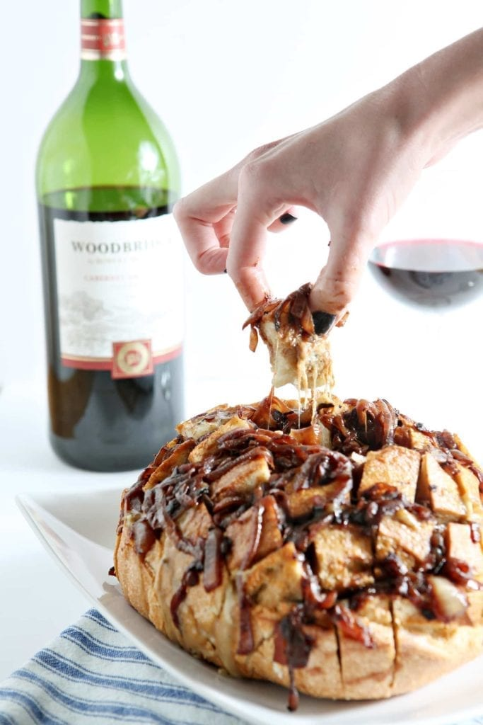A person pulls a bite of Cheesy French Onion Pull-Apart Bread out of the boulle with a bottle of wine and a glass in the background