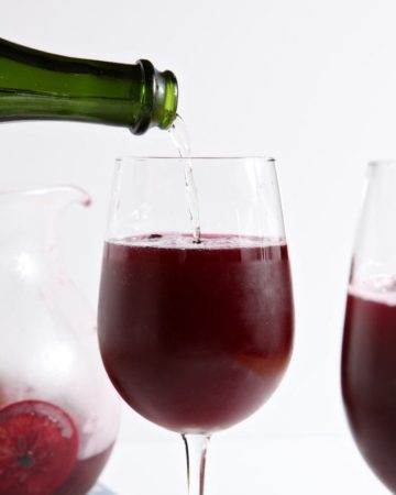 Bottle pouring Champagne in wine glass filled with sangria