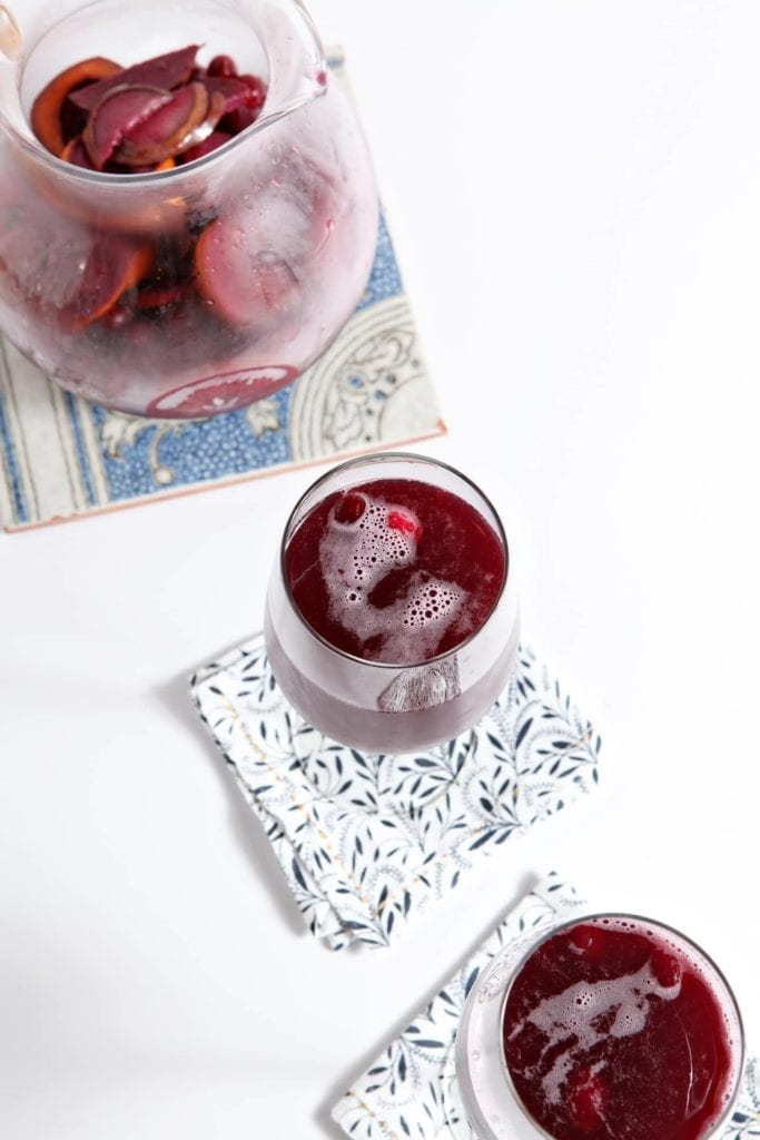 Two glasses of Winter Sparkling Champagne Sangria are served next to a pitcher holding the drink