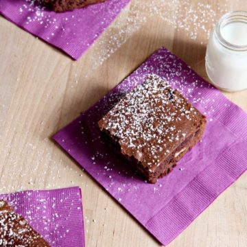 Bourbon Pecan Brownies, served on a wooden platter on purple napkins, with mini glasses of milk.