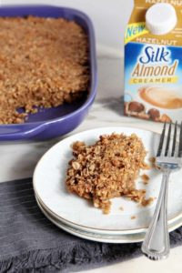 A helping of Hazelnut and Pecan Baked Oatmeal is shown on a white plate with the baking dish of oatmeal and Silk Almond Milk Creamer in the background