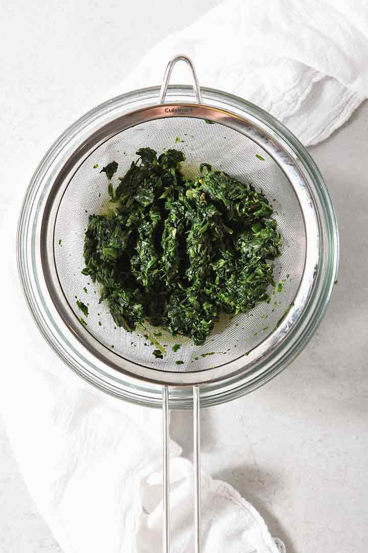 Steamed spinach is shown in a fine mesh strainer, draining