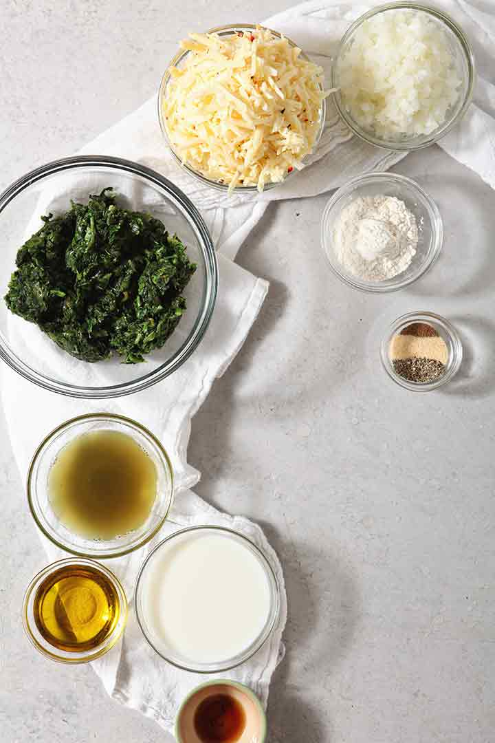 Ingredients for spicy creamed spinach are shown on a background