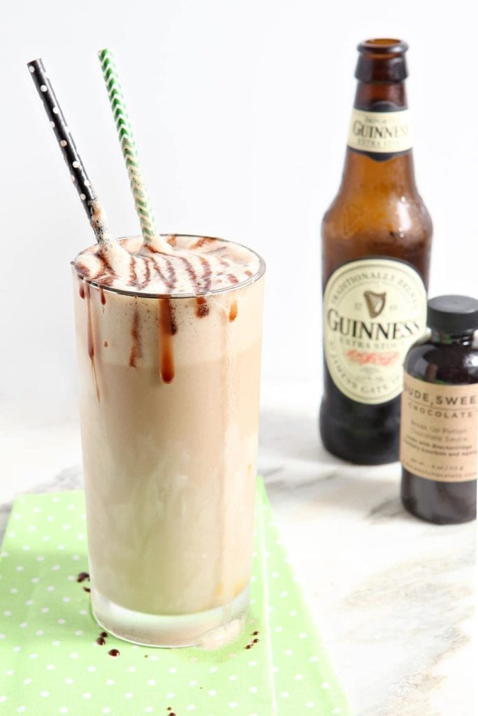A Salted Caramel Guinness Float sits on top of a light green napkin in front of a beer bottle and a bottle of chocolate sauce