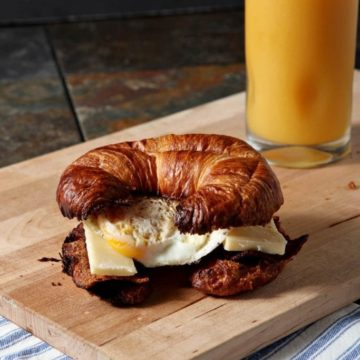 Turkey bacon, sharp cheddar cheese and a fried egg are stacked in a croissant to make the BEST breakfast sandwich for this new year!