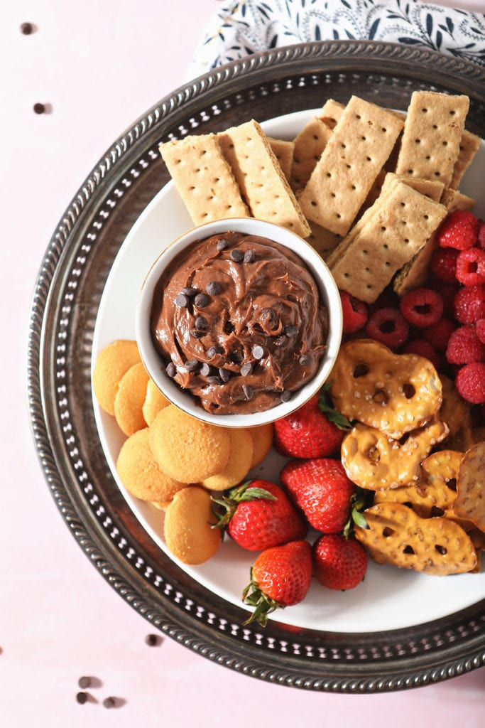 A platter holding chocolate fruit dip surrounded by crackers, fruit and cookies