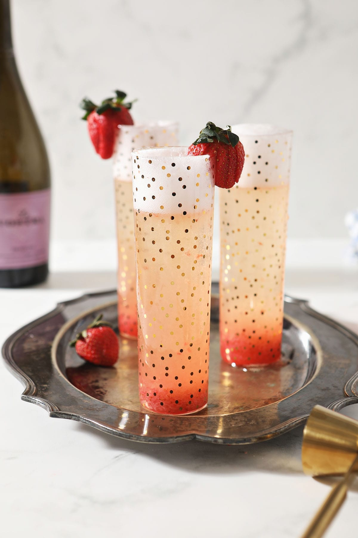 Three Strawberry Champagne Cocktails sit on a silver platter, garnished with fresh strawberries