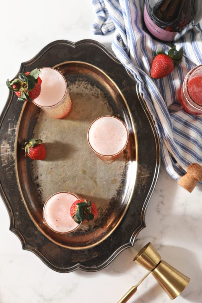 Three Strawberry Champagne mixed drinks sit on a metal tray next to ingredients and a gold jigger